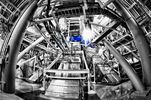 "<h3>NIF Target Bay</h3>This dramatic image of NIF beamlines entering the lower hemisphere of the NIF Target Chamber, as seen from the ground floor of the Target Bay, was taken by NIF photographer Damien Jemison. Five exposures were taken to capture the range of light in the dimly lit Target Bay. Jemison used the high dynamic range (HDR) Efex Pro program to process the five images into a single photo of one of the most spectacular views in the facility. He converted the image to monotone to simplify the chaos while enhancing the drama, then highlighted the barely visible Target Chamber by adding its blue hue back into the image. ""The end result is my artistic view of how I feel when standing face-to-face with the highest-energy laser in the world,"" Jemison said.<br/><br/><a href=""content/assets/images/media/photo-gallery/web/2012-025418-lg.jpg"" target=""_blank"">Download hi-res image</a><br/><a href=""/media/photo-gallery?id=2012-025418"">Direct Link</a>"