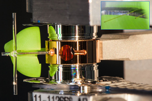 "<h3>Sym Compton Target</h3>The ""sym Compton"" target is a shielding and backlighter development target for the NIF Compton radiography platform (see <a href=""/news/experimental-highlights/2016/march""> ""Testing NIF's Dual-Axis Imager""</a>). The green sphere is an unconverted light shield, which protects two 25-micron-diameter gold wires (see insert), and which are hit with beams from the <a href=""/science/photon-science/arc"">Advanced Radiographic Capability</a> (ARC) to backlight a 200-micron tungsten sphere at the center of the hohlraum. The vertical glass rod is a fiducial (reference point) for the target alignment system to align ARC beams to green shielded backlighter wires. Credit: James Pryatel<br/><br/><a href=""content/assets/images/media/photo-gallery/web/P2380588-lg.jpg"" target=""_blank"">Download hi-res image</a><br/><a href=""/media/photo-gallery?id=p2380588"">Direct Link</a>"
