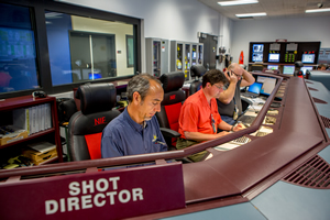"<h3>Hitting the Target</h3>NIF fired its 300th laser target shot in Fiscal Year 2015 on Aug. 13, 2015, meeting the year's goal more than six weeks early. Preparing for the shot in the NIF Control Room are (from left) Shot Director Dean Latray, Operations Manager Bruno Van Wonterghem, and Lead Operator Rod Rinnert (see <a href=""/news/efficiency-improvements/2015/august""> NIF Fires 300th Shot in FY2015</a>).  Credit: Jason Laurea<br/><br/><a href=""content/assets/images/media/photo-gallery/web/p1486134-lg.jpg"" target=""_blank"">Download hi-res image</a><br/><a href=""/media/photo-gallery?id=p1486134"">Direct Link</a>"