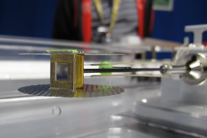 "<h3>TaRT Target</h3>Image of the target used in an April 5, 2015, material strength tantalum Rayleigh-Taylor (TaRT) experiment. The rippled tantalum experimental payload is mounted on a large x-ray drive hohlraum, and the green puck in the background is the backlighter package. The TaRT experiments test the material strength of a tantalum sample at five megabars of pressure (five million times Earth's atmospheric pressure) by measuring the growth of Rayleigh-Taylor  hydrodynamic instabilities (see <a href=""/news/experimental-highlights/2014/november#hgr"">""Controlling Hydrodynamic Mixing in NIF Implosions""</a>).<br/><br/><a href=""content/assets/images/media/photo-gallery/web/tart_target_lg.jpg"" target=""_blank"">Download hi-res image</a><br/><a href=""/media/photo-gallery?id=img_0924"">Direct Link</a>"