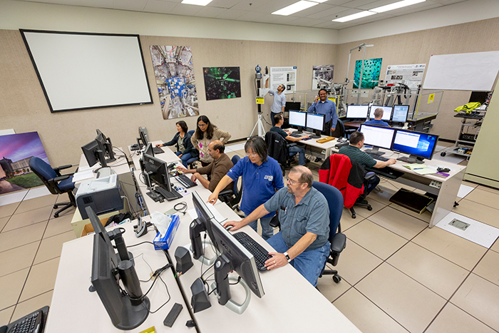 Workers Run Simulations in Testing Facility