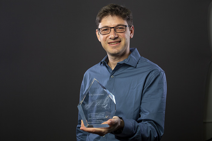 Photo of Eyal Feigenbaum holding SPIE award