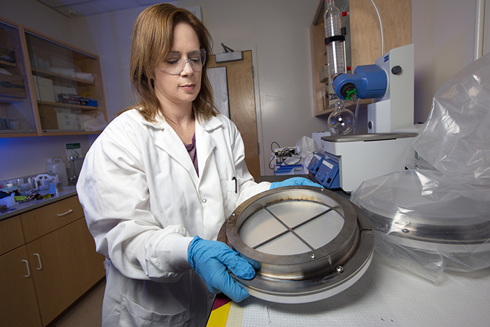 Dawn Shaughnessy examines a sample plate from NIF.