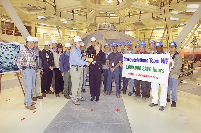 Photo of Tauscher helping NIF employees commemorate a safety milestone